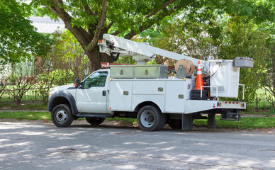 Parked telecommunications vehicle on shaded neighborhood street.
