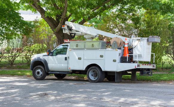 Parked telecommunications vehicle on shaded neighborhood street.