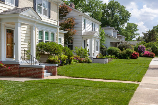 Beautifully manicured residential neighborhood lawns with well-maintained homes.