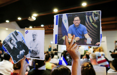 A woman holds up a picture of the journalist Miguel Mora during an event to commemorate the World Day of Press Freedom in Managua