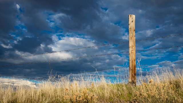 Rusty barbed wire fence against western skies in the American West