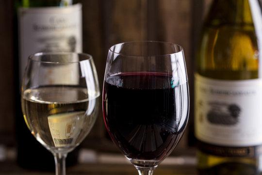 木の背景で赤ワインと白ワインのボトルとワイングラスがオシャレにおいてあるワインバー