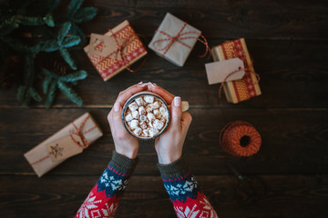 Merry Christmas and happy holidays. Woman hands with cup of coffee. Presents, decoration, pine cones, anise stars, fir branches on rustic wooden background. Christmas family traditions. Toned image.