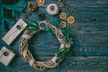 Christmas gift, rustic wreath with decorations, pine cones, fir branches on wooden brown background. Merry Christmas and Happy Holidays concept. Top view. Toned image. Vintage style. Soft focus.
