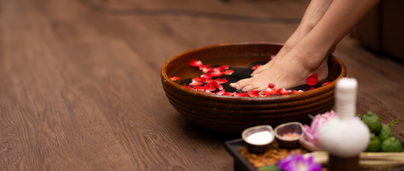 Foto auf Acrylglas Pediküre Closeup shot of a woman feet dipped in water with petals in a wooden bowl