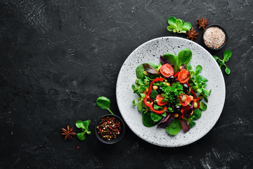 Vegetable salad with spinach, tomatoes, paprika and pumpkin seeds in a plate on a wooden background...