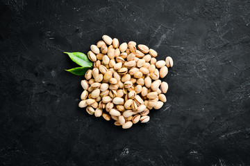Pistachios on a black background. Top view. Free space for your text.