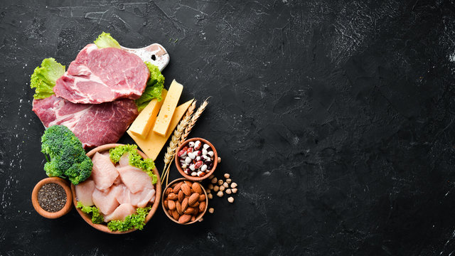 Assortment of healthy protein source and body building foods. Meat, chicken fillet, broccoli, beans, cheese, eggs, wheat. On a stone background.