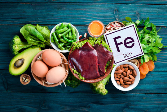 Food containing natural iron. Fe: Liver, avocado, broccoli, spinach, parsley, beans, nuts, on a blue background. Top view.