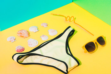 Fashionable art set with yellow bikini panties, sunglasses, drinking straw and sea shells in bright...