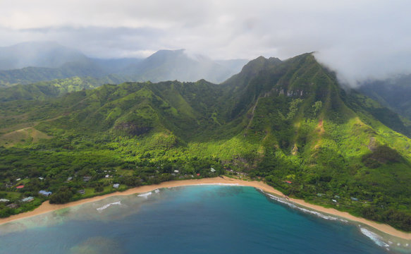 Aerial view over blue bay, golden beach, green mountains and misty clouds in Na Pali Coast State Wilderness Park, landscape photo taken from a helicopter, Kauai, Hawaii, USA