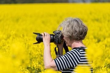 Fotografin mitten in einem Rapsfeld in voller Blüte im Frühjahr