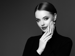 Obraz Beautiful Young Woman with Clean Fresh Skin. Perfect Makeup. Beauty Fashion. Plump Lips. Cosmetic Eyeshadow. Smooth Hair. Girl in Black Turtleneck. Black and white photo - fototapety do salonu