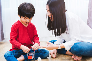 Baby child boy kindergarten playing toy with beautiful mother