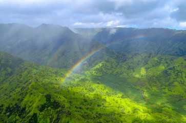 Rainbow over green valley and mountains, panorama shot from a helicopter at Na Pali Coast State Wilderness Park, Kauai, Hawaii, USA