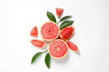 Fototapete - Grapefruits and leaves on white background, top view. Citrus fruits