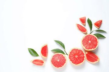 Fototapete - Frame made of grapefruits and leaves on white background, top view with space for text. Citrus fruits