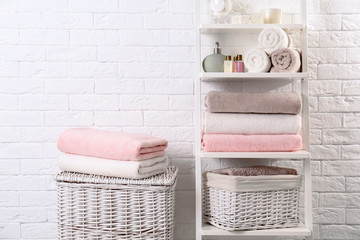 Shelving unit and baskets with clean towels and toiletries near brick wall