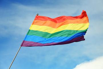 Bright rainbow gay flag fluttering against blue sky. LGBT community