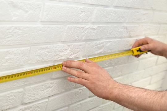 Man measuring brick wall indoors, closeup. Construction tool