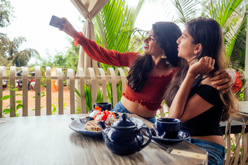 fashionable indian friends couple of two woman making selfie mobile phone.friends long-awaited meeting gossip students eating pancake drinking masala tea after shopping.summer instahram lifestyle