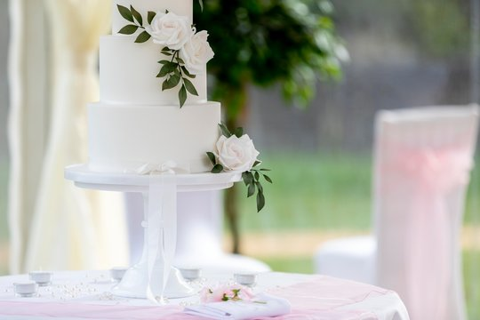 Close up of elegant minimalist wedding cake decorated with white roses on a table in a traditional summer marquee