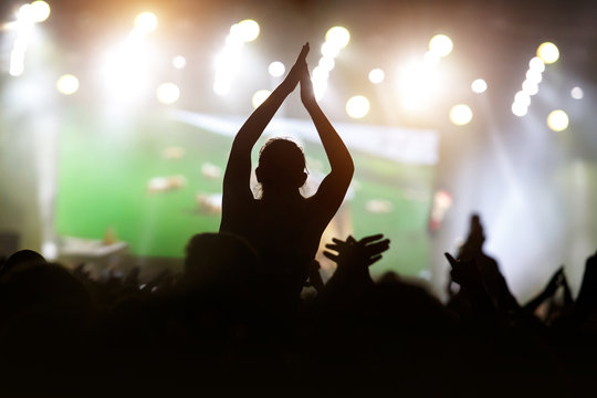 Man with hands up against a music festival scene