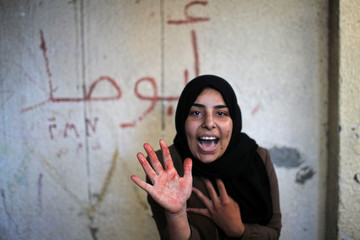 Sister of Palestinian militant Emad Naseer, who was killed in an Israeli air strike, reacts with her hand stained with his blood, during his funeral in the northern Gaza Strip