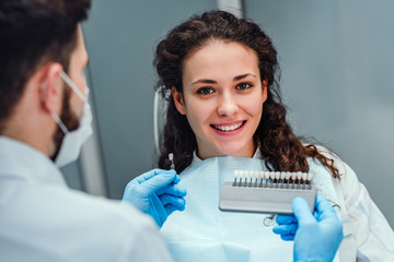 Choice of tooth color with a special scale. Dentist select a shade of tooth enamel for the young pretty girl of the patient. Bleaching, prosthetics, orthopedic dentistry.