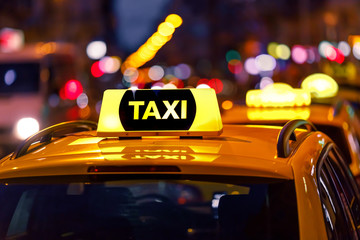 Yellow taxi cab and blurred city lights background at night with colorful bokeh Fototapete