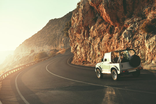 SUV car driving along empty country road at golden summer sunset. People traveling, road trip on lycian way through beautiful mountains coast scenery in sunny summer. Happy journey concept
