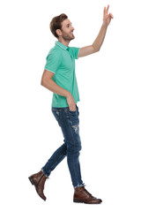 side view of a man walking while showing v sign