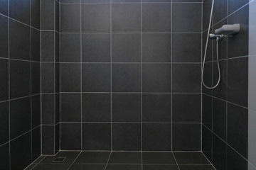 black tile wall and floor in bathroom