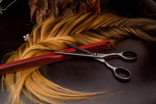 Hairdresser's hands and professional tools, scissors, combs, hair dryer, close-up