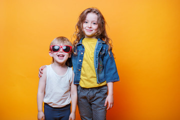 Happy liitle brother and sister on orange background