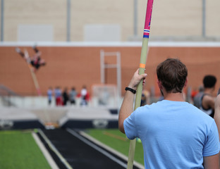 A high school pole vaulter waits his turn to compete.