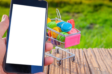 Macarons in small metal shopping cart and smartphone on green background