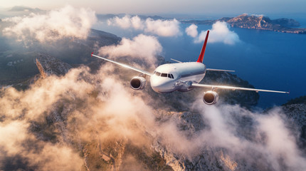 Obraz Airplane is flying over mountains and low clouds at sunset in summer. Landscape with passenger airplane, sky in clouds, rocks, sea, sunlight. Business travel. Commercial plane. Aerial view of aircraft - fototapety do salonu