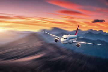 Obraz Airplane in motion. Aircraft with motion blur effect is flying over hills and mountains at sunset. Passenger airplane, blurred clouds. Passenger aircraft in motion. Business travel. Commercial.Concept - fototapety do salonu