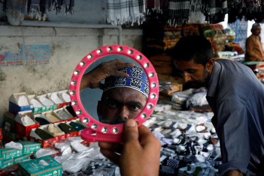A man looks at himself in a mirror while shopping for a cap at a stall outside a mosque, ahead of the holy fasting month of Ramadan, in Karachi