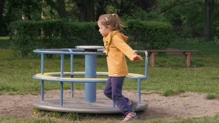 a2721bb15 0:12 Funny little kid girl play in a park playground spinning the carousel