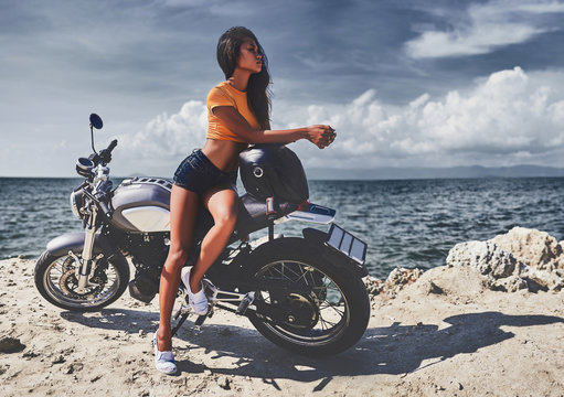 sexy asian woman near her vintage custom motorcycle
