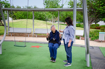 Elderly woman enjoys swinging on the swing set during a daily walk with a female caregiver.