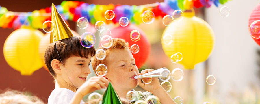 Boys playing with soap bubbles during birthday party for children
