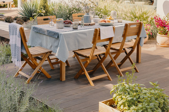 Real photo of a dining table with wooden chairs set on the terrace
