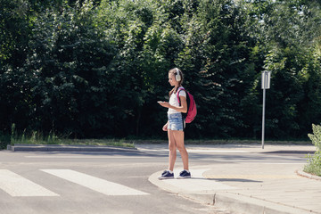 Pretty teenage schoolgirl with headphones and mobile phone on pedestrian crossing