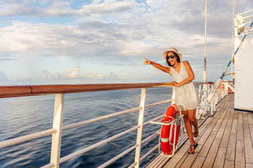 Wall Mural - Happy cruise vacation fun travel woman pointing watching whales or wildlife sighting from deck of boat on Europe summer destination cruising vacation holiday. Luxury relaxation getaway.
