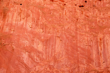 Papiers peints Brique Natural background of a red sandstone bluff with cracks and eroded holes and water washes - beautiful