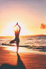 Yoga wellness retreat class on morning sunrise beach landscape. Silhouette of girl standing in tree pose meditation vertical background.
