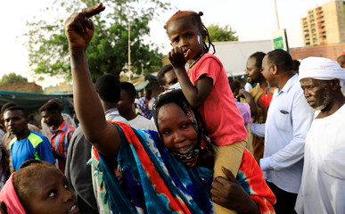 A Sudanese protester makes victory sign as she carries her daughter during a demonstration in front of  the defense ministry compound in Khartoum